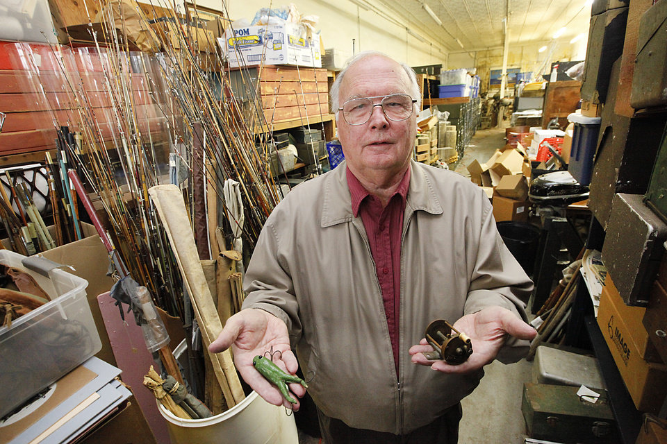 Karl White of Luther holds a George Snyder reel, the first casting reel made in the United States, and a Heddon Frog, the first lure made by the Heddon Lure Company in 1898.  Photo By David McDaniel, The Oklahoman