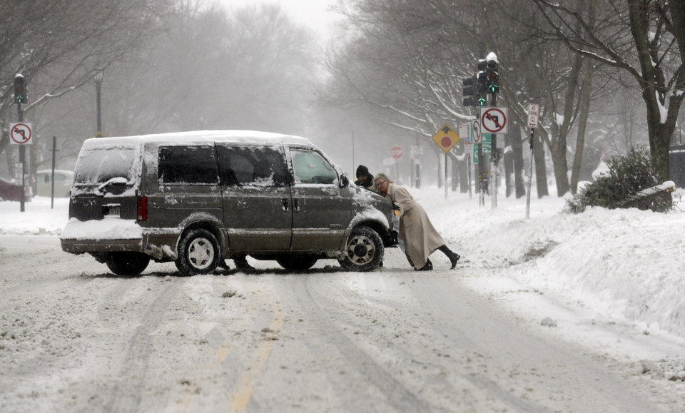 Photo - People push a car on a snowy road in Chicago on Sunday, Jan. 5, 2014. Sunday night temperatures will drastically drop to about minus 20 degrees. (AP Photo/Nam Y. Huh)