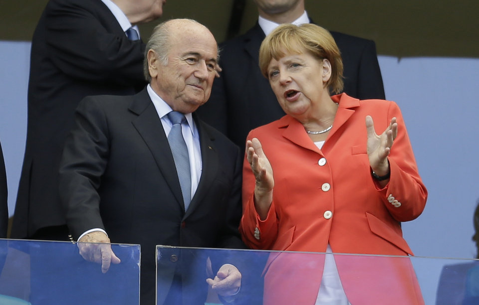 Photo - German chancellor Angela Merkel, right, talks to FIFA President Sepp Blatter prior to the group G World Cup soccer match between Germany and Portugal at the Arena Fonte Nova in Salvador, Brazil, Monday, June 16, 2014.  (AP Photo/Natacha Pisarenko)