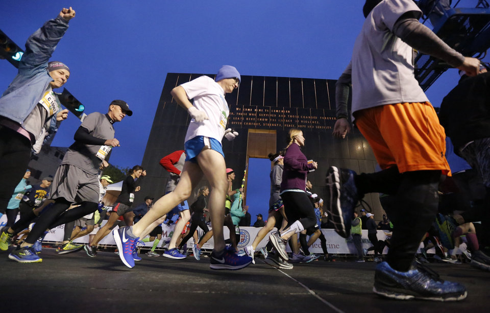 Photo -  Runners stream past the 9:03 gate at the start of the 2017 Oklahoma City Memorial Marathon on Sunday. [PHOTO BY SARAH PHIPPS, THE OKLAHOMAN]