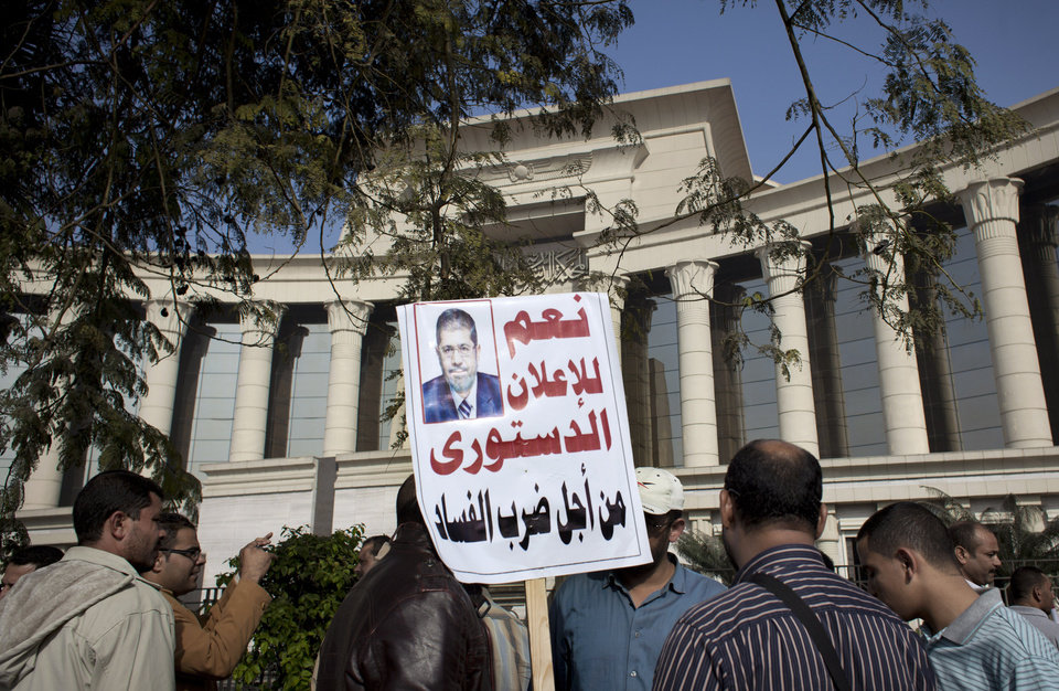 Photo - A supporter of Egyptian President Mohammed Morsi holds a banner with his picture and Arabic that reads,