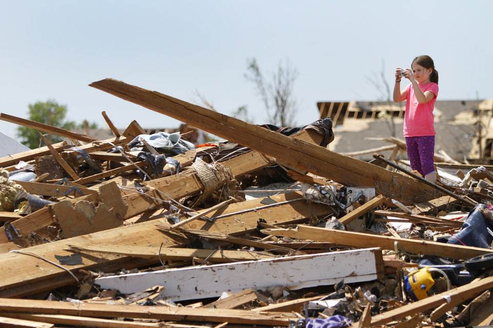 Photo - Lauren Matthews, 7 takes photos of her home on SW 146th in Oklahoma City, Wednesday May 22, 2013. Members of the Oklahoma City Lauren's home was hit by a tornado on Monday afternoon. Photo By Steve Gooch, The Oklahoman