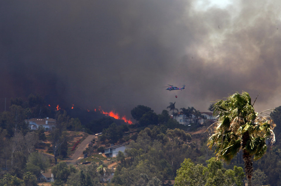 Photo - A helicopter files over San Marcos, Calif. on Thursday, May 15, 2014 as wildfires climb a hill eastward towards Mission Hills High School where the Red Cross has set up an evacuation center. The fires have come during a heat wave in the drought-stricken state. (AP Photo/UT San Diego, Peggy Peattie)