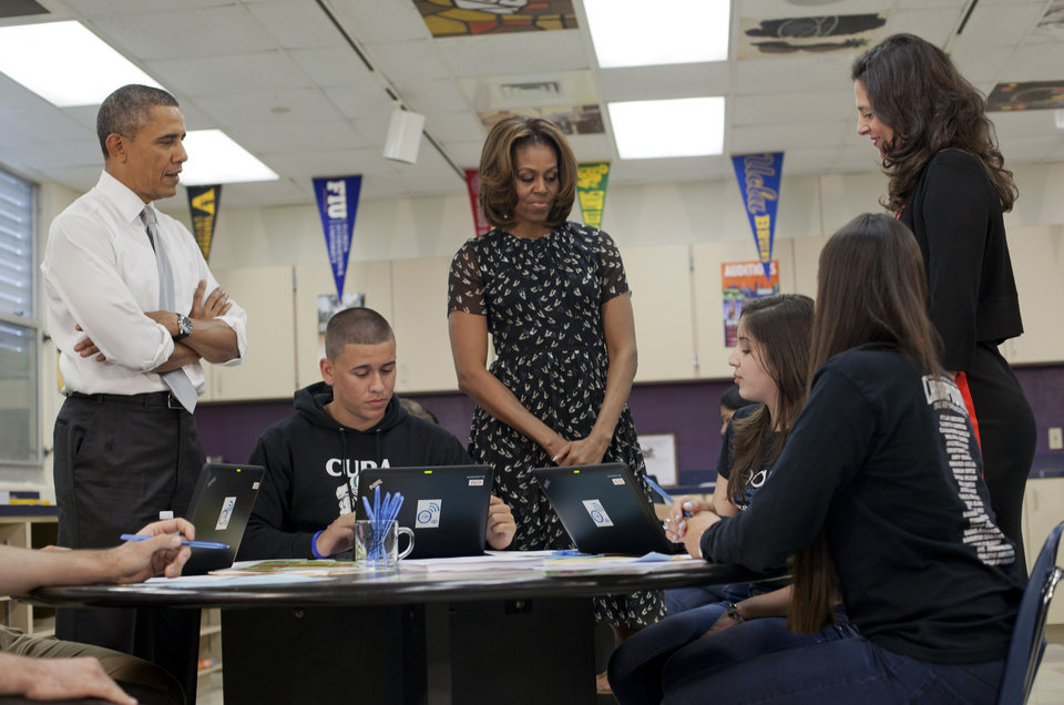 Photo - President Barack Obama, left, and the first lady Micheal Obama, center, and school guidance counselor Amy Shapiro, right, talk with students at Coral Reef High School, Friday, March 7, 2014, in Miami. Obama traveled to the Miami school to unveil a new initiative to ensure more students complete the Free Application for Federal Student Aid (FAFSA), a document required for most types of school financial aid such as Pell grants.  (AP Photo/Pablo Martinez Monsivais)