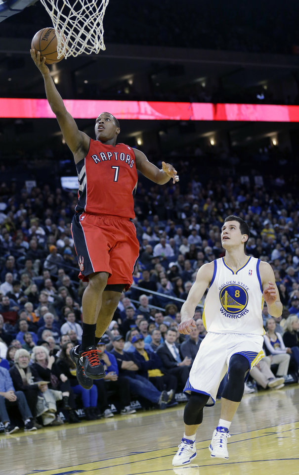 Photo - Toronto Raptors' Kyle Lowry (7) scores past Golden State Warriors' Nemanja Nedovic (8) during the first half of an NBA basketball game on Tuesday, Dec. 3, 2013, in Oakland, Calif. (AP Photo/Marcio Jose Sanchez)