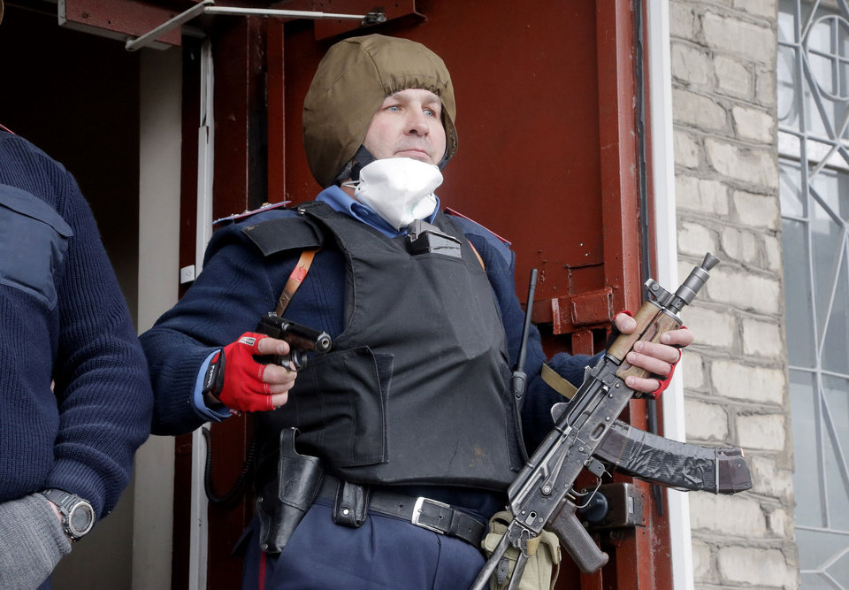 Photo - The head of the local police station Herman Pristupa, brandishes firearms at the entrance to a police headquarters stormed by pro-Russian activists in Horlivka, Ukraine, Monday, April 14, 2014. Ukraine's acting President Oleksandr Turchynov on Monday called for the deployment of United Nations peacekeeping troops in the east of the country, where pro-Russian insurgents have occupied buildings in nearly 10 cities. (AP Photo/Efrem Lukatsky)