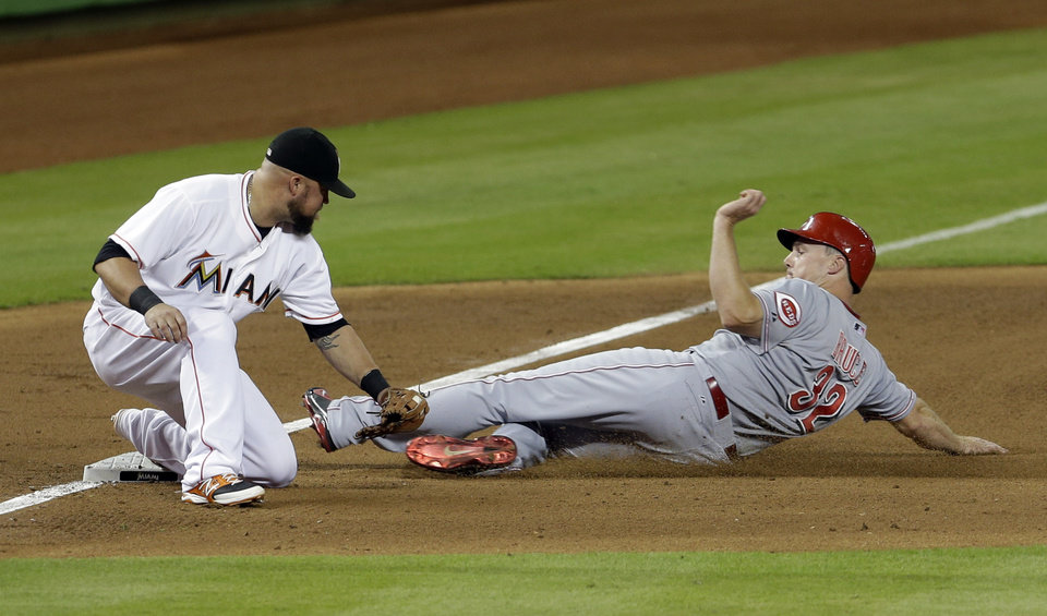 Photo - Cincinnati Reds' Jay Bruce (32) slides safely into third base on a base hit by Todd Frazier as Miami Marlins third baseman Casey McGehee, left, is late on the tag in the fourth  inning of a baseball game in Miami, Friday, Aug.1, 2014. Billy Hamilton scored on the single. (AP Photo/Alan Diaz)