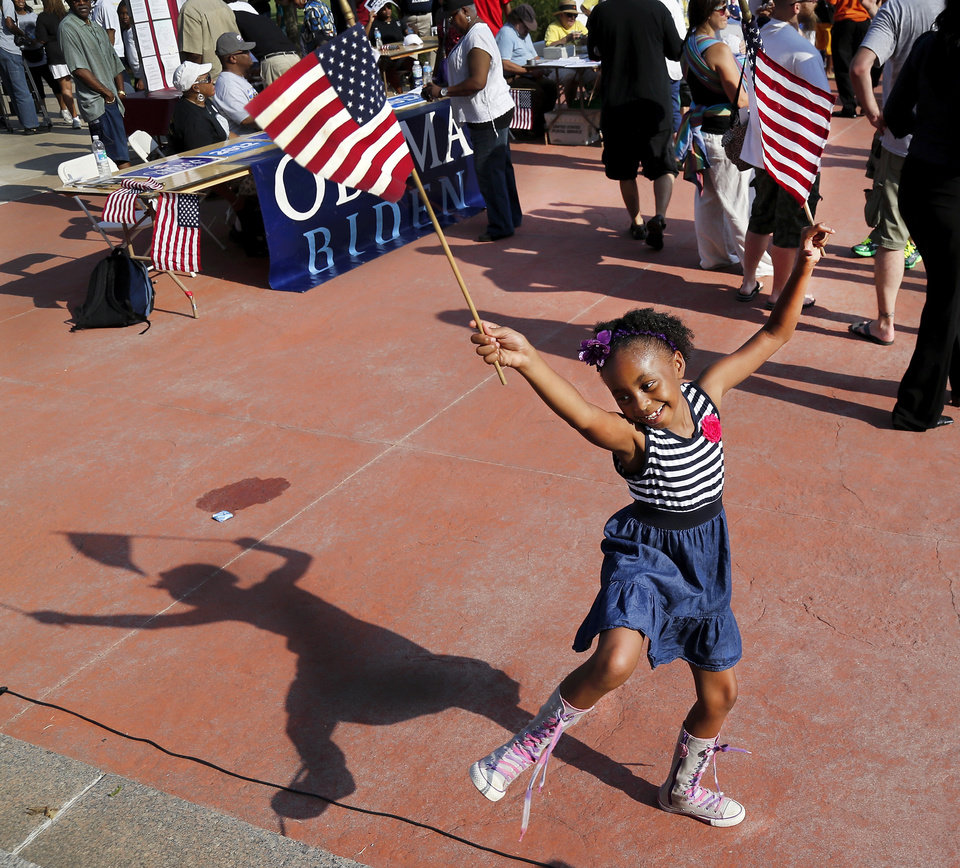 """Peja West, 6, waves a pair of American flags above her head while dancing at the foot of the steps on the north side of the Capitol. West, from Spencer, came to the rally with her grandmother, mother and her baby sister. A diverse crowd of about  300 people rallied on the north side of the State Capitol Saturday morning, Aug. 24, 2013, to commemorate the upcoming 50th anniversary of the  1963 Civil Rights March on Washington.   Most of the crowd marched more than a mile from Stiles Park,  walking up Lincoln Blvd., to the statehouse. Many  in the crowd carried signs or banners, and some wore shirts bearing images of slain civil rights leader Martin Luther King Jr., who delivered his impassioned  oratory to a crowd of nearly 250,000 on the Washington Mall on Aug. 28, 1963.  At the time,  it was the largest demonstration ever seen in the nation's capital. King's remarks to the crowd, now known as the """"I Have A Dream"""" speech, brought a national focus to the civil rights struggle in America and is credited with being a large influence to secure enough votes in Congress for the passage of the Civil Rights Act the following year.    Photo  by Jim Beckel, The Oklahoman."""