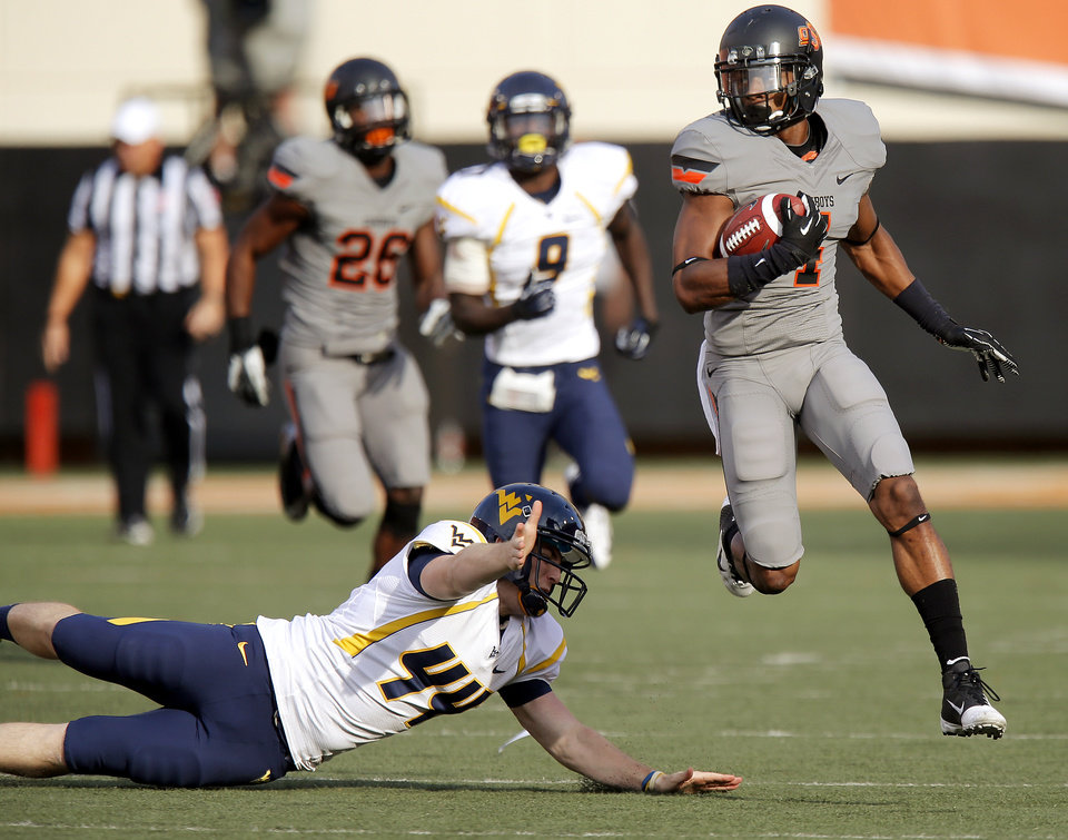 Photo - Oklahoma State's Justin Gilbert (4) leaps past West Virginia's Corey Smith (44) as he returns a kickoff for a touchdown during a college football game between Oklahoma State University (OSU) and West Virginia University at Boone Pickens Stadium in Stillwater, Okla., Saturday, Nov. 10, 2012. Photo by Bryan Terry, The Oklahoman