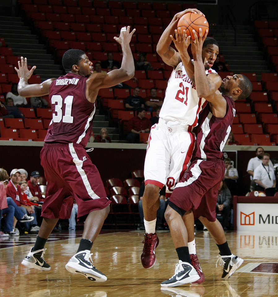Photo - OU's Cameron Clark (21) tries to pass the ball between Mark Robertson (31) and Kevin White (3) of Maryland Eastern Shore during the men's college basketball game between Maryland Eastern Shore and Oklahoma at Lloyd Noble Center in Norman, Okla., Monday, January 3, 2011. OU won, 73-49. Photo by Nate Billings, The Oklahoman