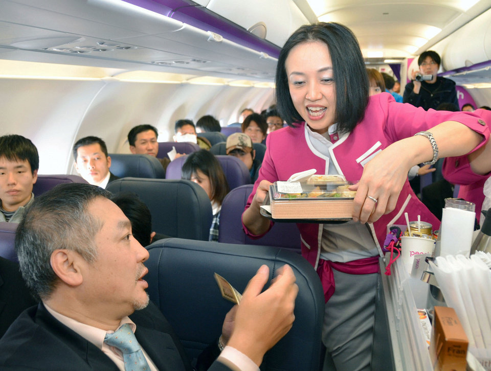 Photo -   In this March 1, 2012 photo, a passenger buys a meal during the first flight by Peach Aviaction from Osaka, western Japan, bound for Sapporo, northern Japan. Japan has a reputation for loving expensive things like overpriced real estate, gourmet melons and luxury brands. But the nation is finally discovering the joy of flying cheap, with the arrival this year of three low-cost carriers. The takeoff of AirAsia Japan, Peach Aviation and Jetstar Japan could change lifestyles. (AP Photo/Kyodo News) JAPAN OUT, MANDATORY CREDIT, NO LICENSING IN CHINA, FRANCE, HONG KONG, JAPAN AND SOUTH KOREA
