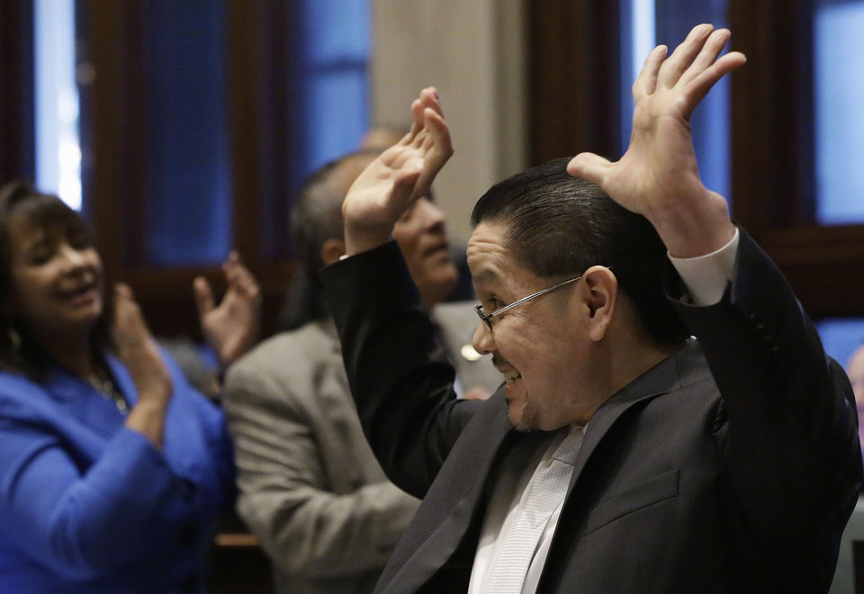 Photo - FILE - In this Jan. 8, 2013 file photo, Illinois state Rep. Edward J. Acevedo, D-Chicago, celebrates as the House passes legislation allowing illegal immigrants to obtain driver's licenses during session at the Illinois State Capitol in Springfield. Gov. Pat Quinn is expected to sign the legislation on Sunday, Jan. 27. as Illinois becomes the fourth and most populous state to issue driver's licenses to illegal immigrants, the initiative is still nagged by concerns it has enough safeguards to avoid the identity fraud and other pitfalls faced by the three other states with similar laws. (AP Photo/Seth Perlman, File)
