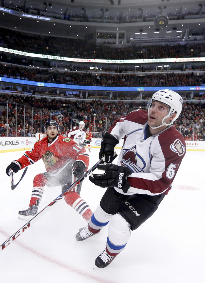 Photo - Chicago Blackhawks center Marcus Kruger (16) and Colorado Avalanche defenseman Andre Benoit (61) keep an on a flying puck during the first period of an NHL hockey game Tuesday, March 4, 2014, in Chicago. (AP Photo/Charles Rex Arbogast)