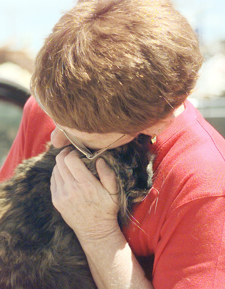 "MAY 3, 1999 TORNADO: TORNADO VICTIM MARGO MIRACLE EMBRACES HER CAT ""SASHA"". MARGO HAD JUST LOCATED TWO OF HER CATS IN A CLOSET ON WEDNESDAY AFTERNOON. HER THREE CATS SURVIVED, BUT SHE HAD TO PUT TO SLEEP HER INJURED DOG."