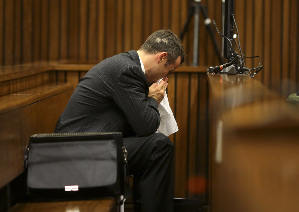 Photo - Oscar Pistorius blows his nose  after reaching for a bucket as he listened to cross questioning about the events surrounding the shooting death of his girlfriend Reeva Steenkamp, in his second week in court during his trial in Pretoria, South Africa, Monday, March 10, 2014. Pistorius is charged with the shooting death of his girlfriend  Steenkamp, on Valentines Day in 2013. (AP Photo/Siphiwe Sibeko, Pool)