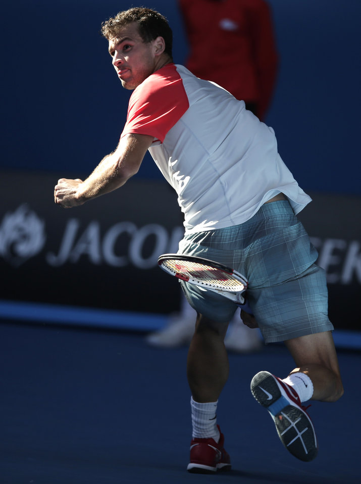 Photo - Grigor Dimitrov of Bulgaria hits a return between legs to Rafael Nadal of Spain during their quarterfinal at the Australian Open tennis championship in Melbourne, Australia, Wednesday, Jan. 22, 2014.(AP Photo/Rick Rycroft)