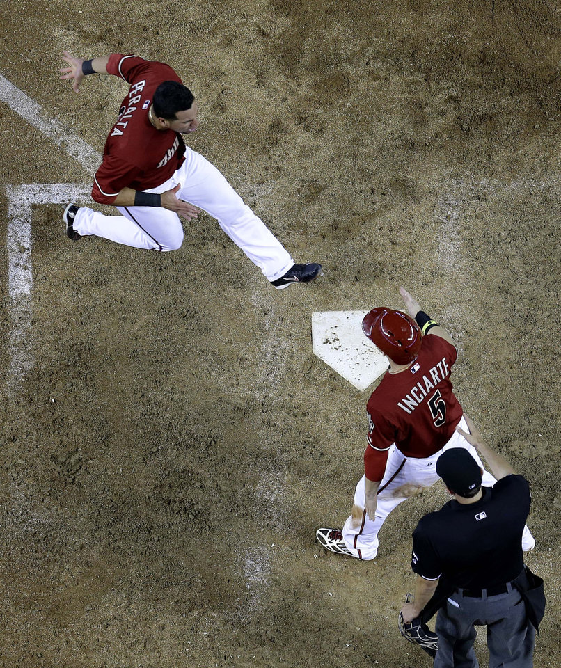 Photo - Arizona Diamondbacks' David Peralta, left, cross home plate after Ender Inciarte to score the game winning run on a two RBI double by teammate Paul Goldschmidt against the Miami Marlins during the 10th inning of a baseball game, Wednesday, July 9, 2014, in Phoenix. The Diamondbacks won 4-3 in 10 innings. (AP Photo/Matt York)