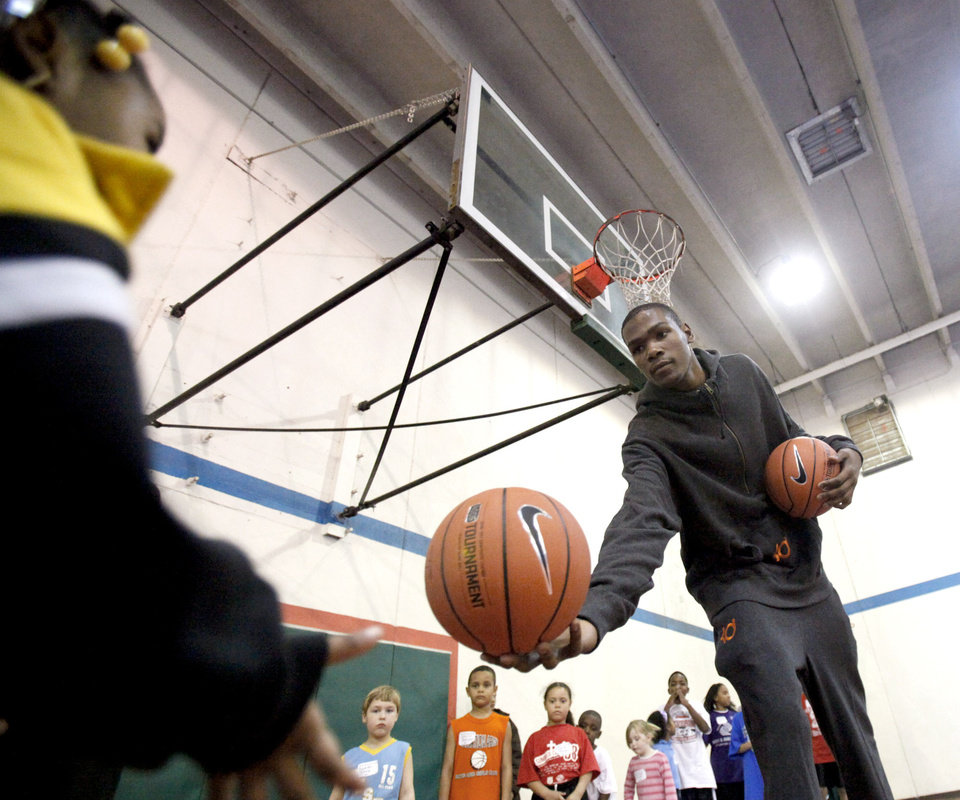 Photo - Kevin Durant hands a ball to Imani Jackson during shooting drills at the Nike Clinic at the Salvation Army Boy and Girls  Club, Saturday, Feb. 7, 2009, in Oklahoma City. PHOTO BY SARAH PHIPPS, THE OKLAHOMAN