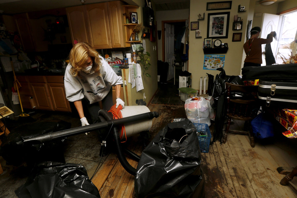 Photo - Kathleen Seemar, left, and her 13-year-old son, Andrew Seemar, clean up their home after it was flooded during superstorm Sandy, Thursday, Nov. 1, 2012, in Brick, N.J. Three days after Sandy slammed the mid-Atlantic and the Northeast, New York and New Jersey struggled to get back on their feet, the U.S. death toll climbed to more than 80, and more than 4.6 million homes and businesses were still without power.  (AP Photo/Julio Cortez) ORG XMIT: NJJC118