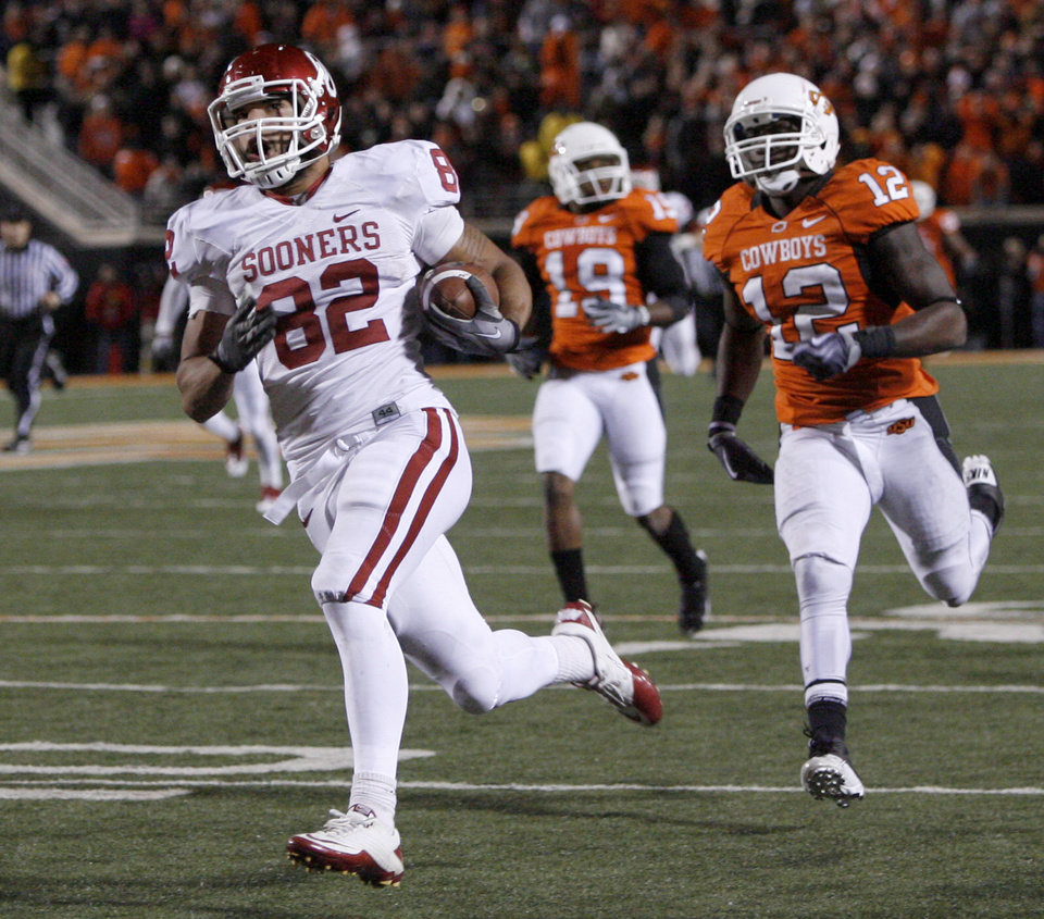 Photo - Oklahoma's James Hanna (82) scores on a long touchdown pass in front of Oklahoma State's Johnny Thomas (12) during the Bedlam college football game between the University of Oklahoma Sooners (OU) and the Oklahoma State University Cowboys (OSU) at Boone Pickens Stadium in Stillwater, Okla., Saturday, Nov. 27, 2010. Photo by Bryan Terry, The Oklahoman