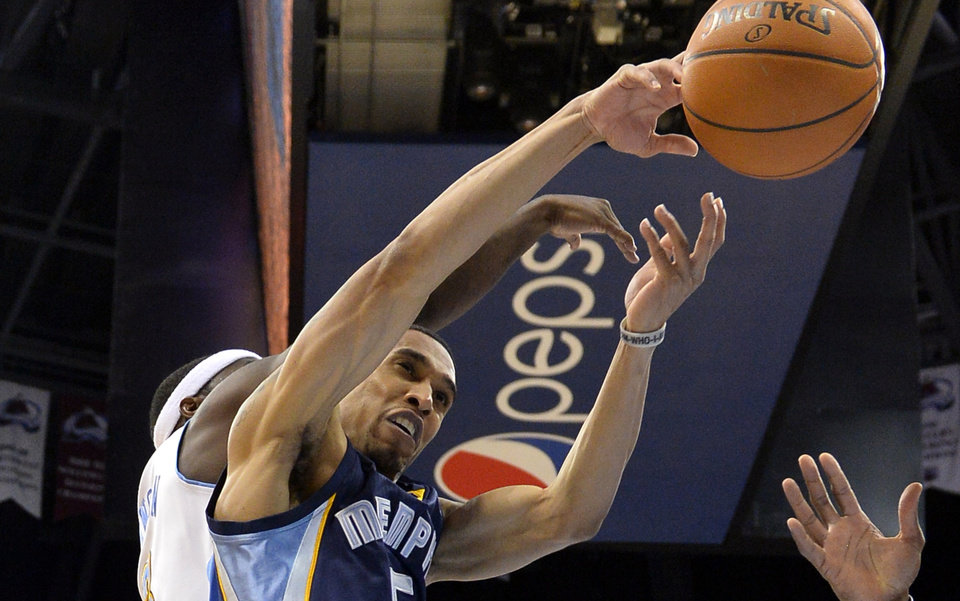 Photo - Memphis Grizzlies guard Courtney Lee (5) goes up for a rebound against Denver Nuggets guard Ty Lawson (3) during the second quarter of an NBA basketball game on Monday, March 31, 2014, in Denver. (AP Photo/Jack Dempsey)