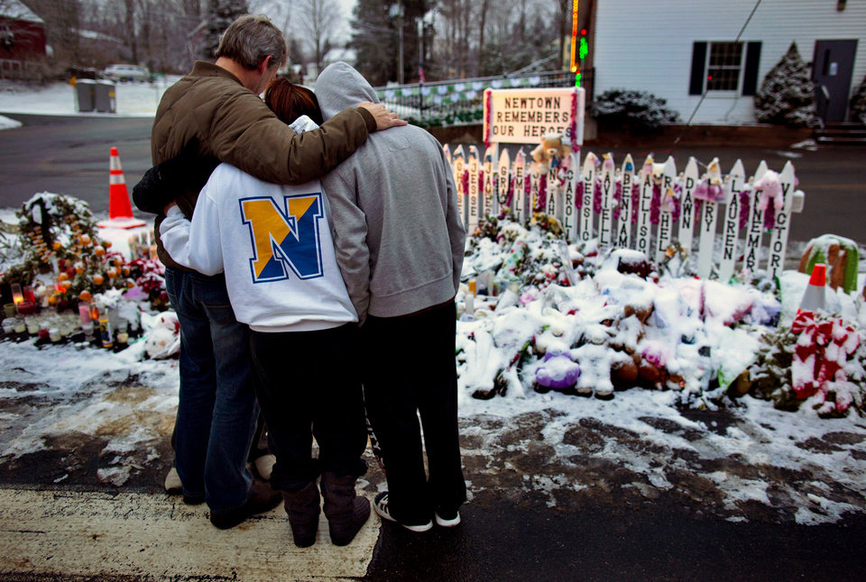 Photo - Members of the Rutter family of Sandy Hook, Conn., embrace early Christmas morning as they stand near memorials by the Sandy Hook firehouse in Newtown, Conn.,Tuesday, Dec. 25, 2012. People continue to visit memorials after gunman Adam Lanza walked into Sandy Hook Elementary School in Newtown, Conn., Dec. 14, and opened fire, killing 26, including 20 children, before killing himself.  (AP Photo/Craig Ruttle)