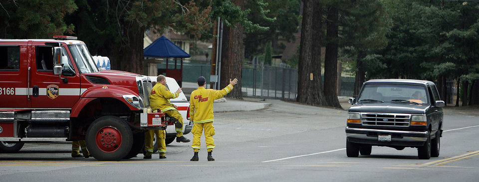 Photo - Cal Fire firefighters wave to residents returning to Idyllwild on Highway 243 after the evacuation order was rescinded in the areas affected by the Mountain Fire on Sunday, July 21, 2013. Thousands of people were allowed to return to their homes in Southern California mountain communities near Palm Springs on Sunday, after firefighters aided by heavy rain made substantial progress against a week-old wildfire that has burned across 42 square miles and destroyed seven homes.  (AP Photo/The Press-Enterprise, Terry Pierson)
