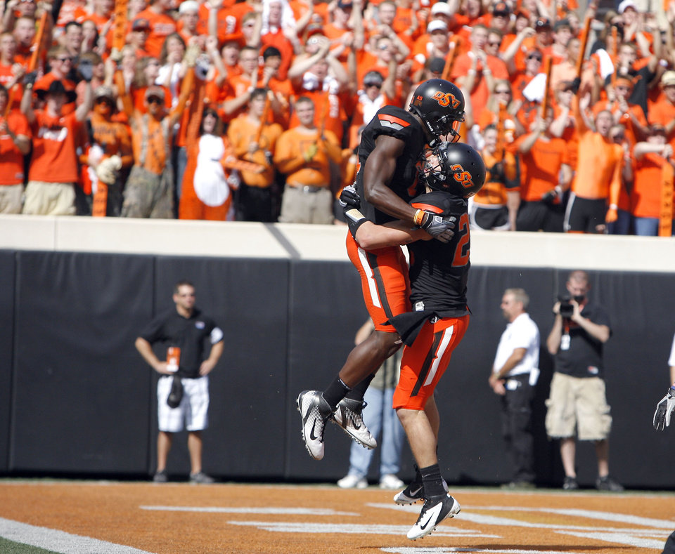 Photo - Oklahoma State's Justin Blackmon (81) and Josh Cooper (25) celebrate a touchdown during the first half of the college football game between the Oklahoma State University Cowboys (OSU) and the University of Kansas Jayhawks (KU) at Boone Pickens Stadium in Stillwater, Okla., Saturday, Oct. 8, 2011. Photo by Sarah Phipps, The Oklahoman