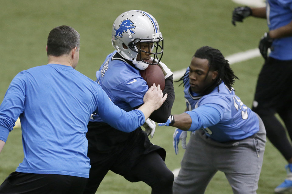 Photo - Detroit Lions running back Montell Owens, center, runs through drills at the NFL football team's training facility in Allen Park, Mich., Tuesday, April 22, 2014. (AP Photo/Carlos Osorio)