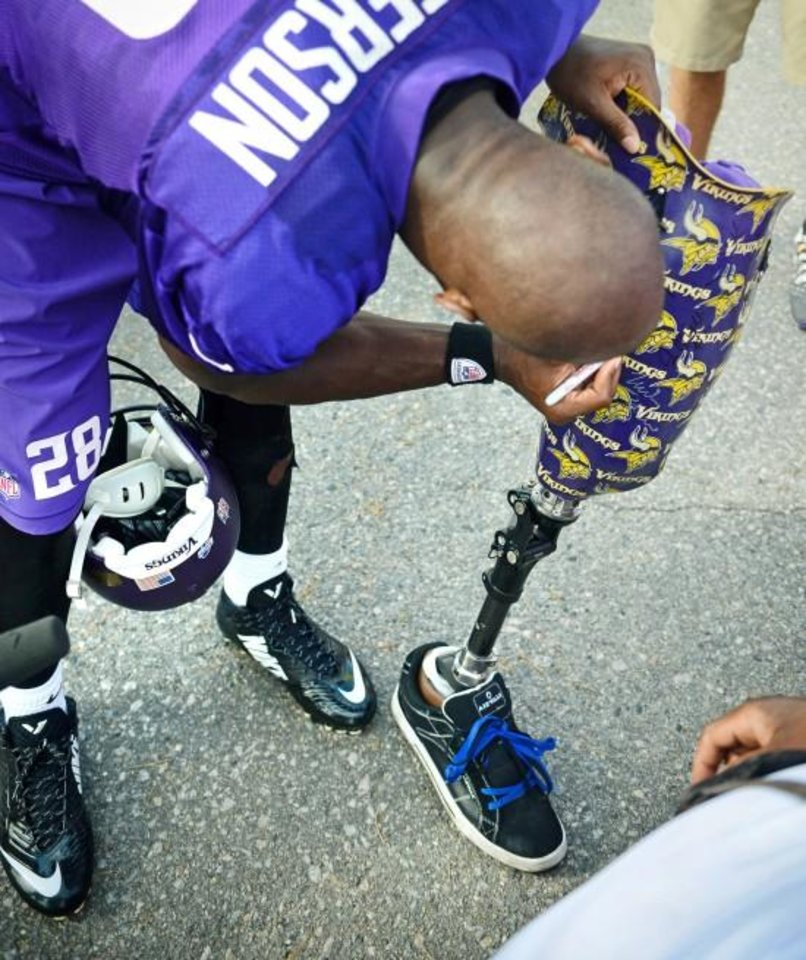 Photo -  Minnesota Vikings running back Adrian Peterson signs an autograph on a fan's prosthetic leg on the last day of the NFl football team's training camp, in Mankato, Minn. on Thursday, Aug. 14, 2014. (AP Photo/St. Paul Pioneer Press, Ben Garvin)