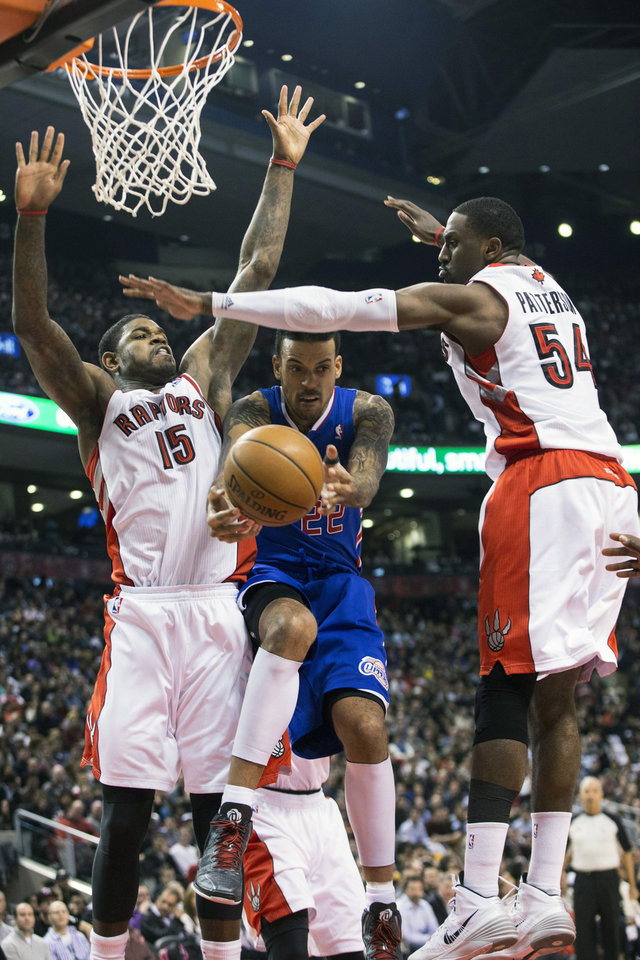 Photo - Los Angeles Clippers' Matt Barns, center,  looks to pass between Toronto Raptors' Amir Johnston, left, and Patrick Patterson during the first half of an NBA basketball game, Saturday, Jan. 25, 2014 in Toronto. (AP Photo/The Canadian Press, Chris Young)