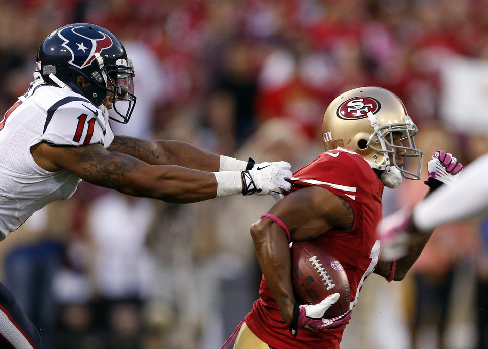 Photo - San Francisco 49ers wide receiver Kyle Williams, right, carries the ball as Houston Texans wide receiver DeVier Posey pulls his jersey in the first half of an NFL football game in San Francisco, Sunday, Oct. 6, 2013.  (AP Photo/Beck Diefenbach)