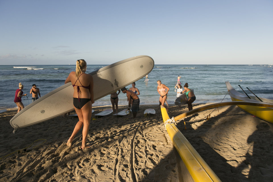 Photo - A group of tourists from California head into the water for a surf lesson in Waikiki in Honolulu on Thursday, Aug. 7, 2014. With Iselle, Hawaii is expected to take its first direct hurricane hit in 22 years. Tracking close behind it is Hurricane Julio. (AP Photo/Marco Garcia)