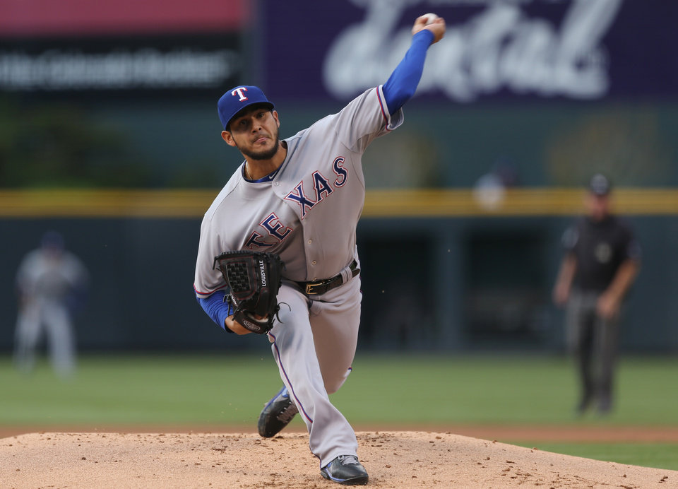 Photo - Texas Rangers starting pitcher Martin Perez works against the Colorado Rockies in the first inning of an interleague baseball game in Denver on Monday, May 5, 2014. (AP Photo/David Zalubowski)