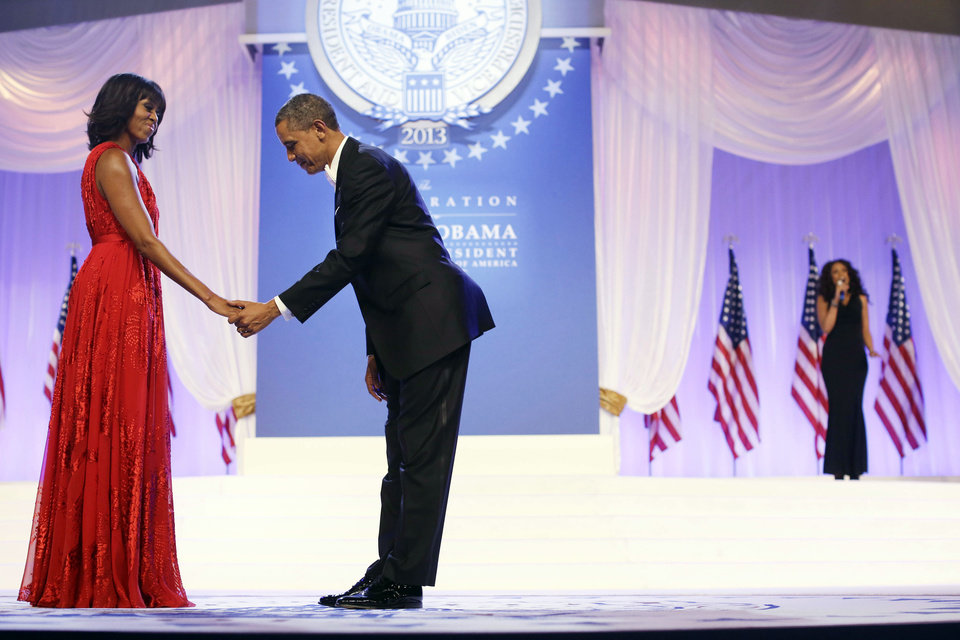 Photo - President Barack Obama bows as he and first lady Michelle Obama, wearing a ruby colored chiffon and velvet Jason Wu gown, gets ready to dance as singer Jennifer Hudson, right, sings Al Green's