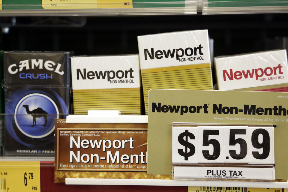 Photo - Camel, a Reynolds American brand, and Newport, a Lorillard brand, cigarettes are displayed for sale, Tuesday, July 15, 2014, in Doral, Fla. Cigarette maker Reynolds American Inc. is planning to buy rival Lorillard Inc. for about $25 billion in a deal to combine two of the nation's oldest and biggest tobacco companies. (AP Photo/Lynne Sladky)