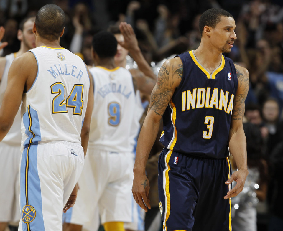Photo - Indiana Pacers guard George Hill, front right, turns away as Denver Nuggets guard Andre Miller, front left, joins teammates as they congratulate Andre Iguodala after he hit the winning free throw in the fourth quarter of the Nuggets' 102-101 victory in an NBA basketball game in Denver on Monday, Jan. 28, 2013. (AP Photo/David Zalubowski)