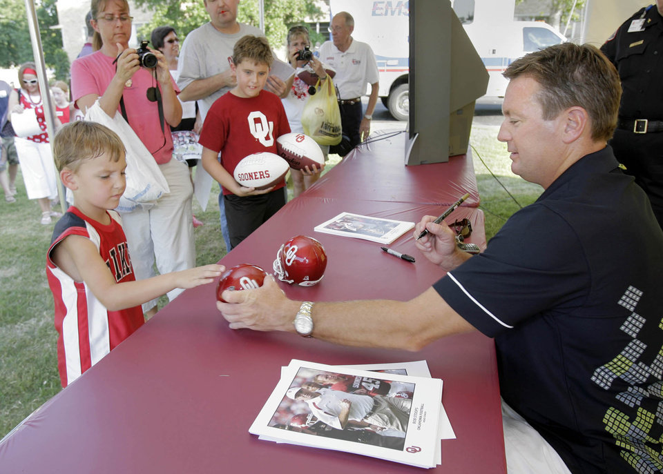 Photo - University of Oklahoma college football head coach Bob Stoops (right) signs autographs for fans during the OU Caravan stop at the OU Schusterman Center in Tulsa, OK June 25, 2009. MICHAEL WYKE/Tulsa World
