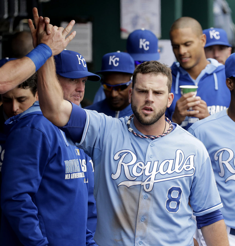 Photo - Kansas City Royals' Mike Moustakas celebrates in the dugout after hitting a three-run double during the second inning of a baseball game against the Colorado Rockies Wednesday, May 14, 2014 in Kansas City, Mo. (AP Photo/Charlie Riedel)