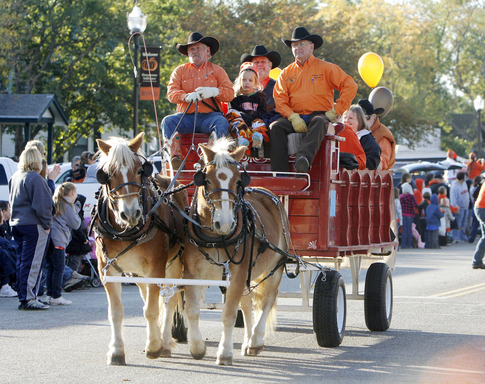 Photo - OSU fans ride in a wagon in the Oklahoma State Cowboy's homecoming parade in downtown Stillwater, OK, Saturday, Oct. 29, 2011. By Paul Hellstern, The Oklahoman