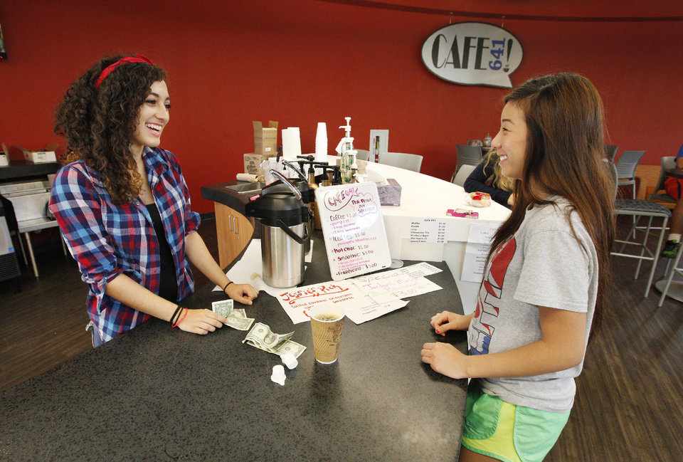 Photo - Junior Jordan Tarter, 16, serves coffee to Jennifer Phan, 17, in the new media center.