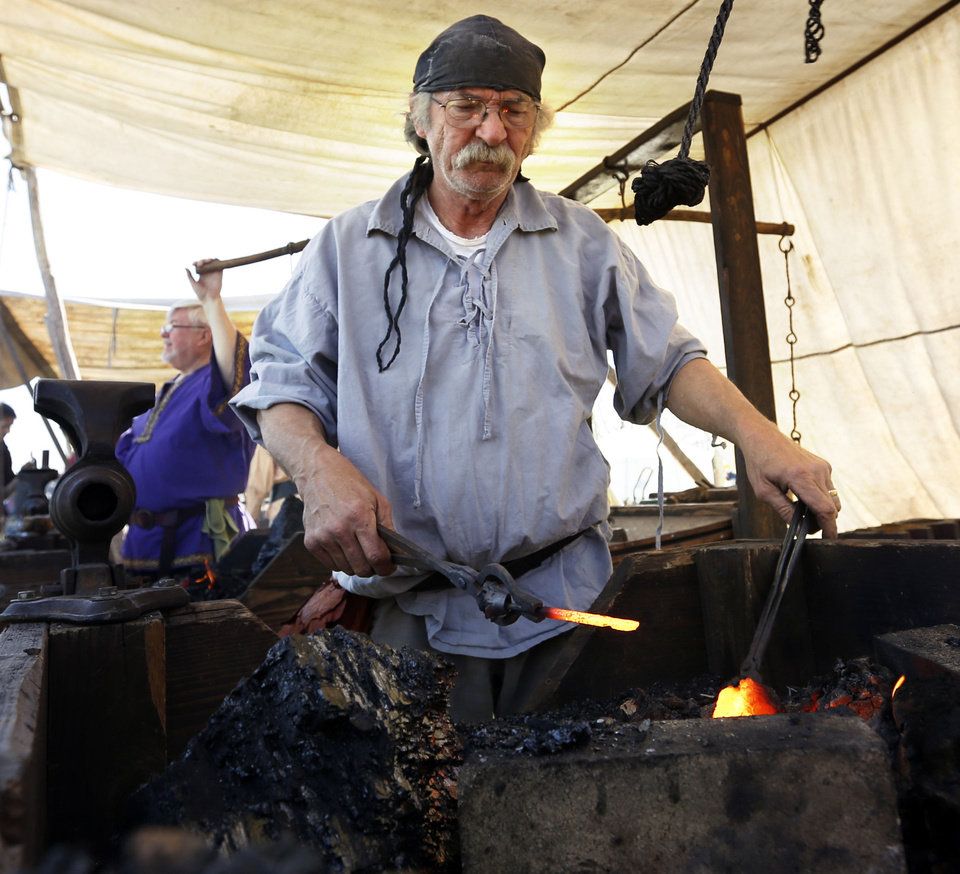 Left: Terry Jenkins, a blacksmith from Blanchard, works iron Friday at Reaves Park.
