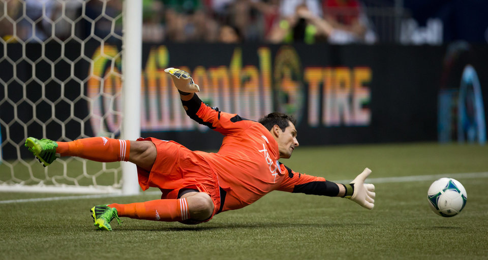 Seattle Sounders' goalkeeper Michael Gspurning, of Austria, allows a goal to Vancouver Whitecaps' Kenny Miller, of Scotland, during the first half of an MLS soccer  match in Vancouver, British Columbia, on Saturday, July 6, 2013. (AP Photo/The Canadian Press, Darryl Dyck)
