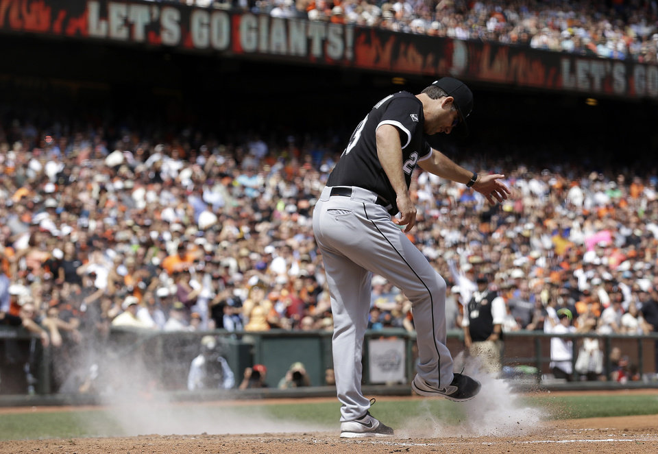 Photo - Chicago White Sox manager Robin Ventura kicks dirt over the plate after being ejected for arguing a call on San Francisco Giants' Gregor Blanco, who was originally ruled out at home but then ruled safe after review, during the seventh inning of a baseball game against the San Francisco Giants in San Francisco, Wednesday, Aug. 13, 2014. (AP Photo/Jeff Chiu)