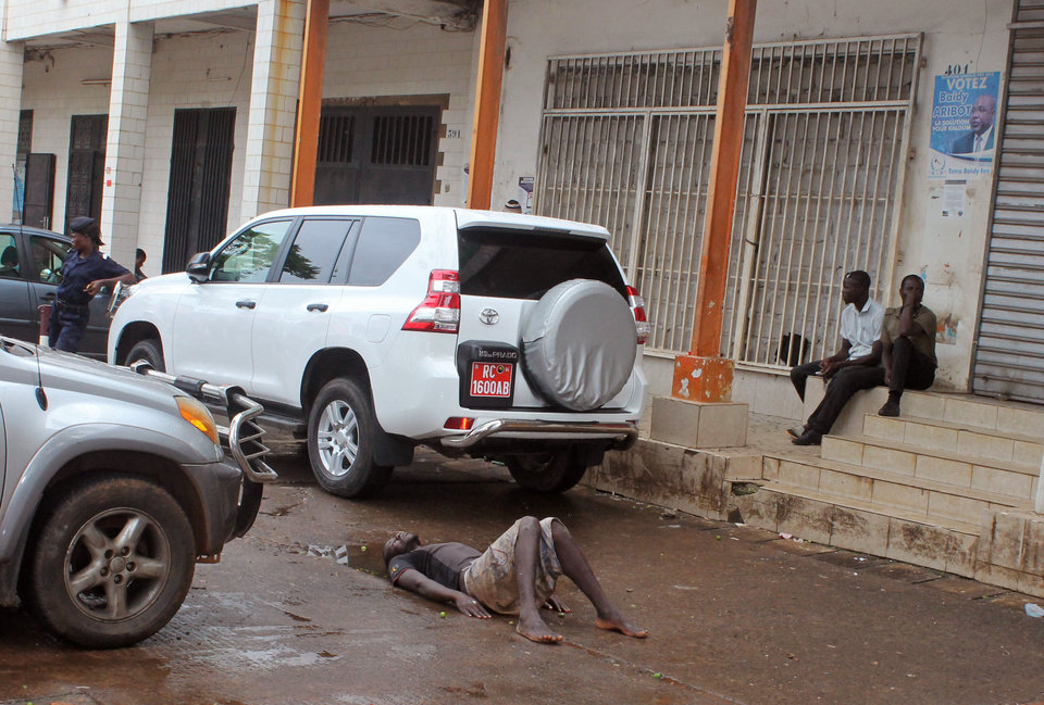 Photo - Guinea Police secure the area around a man who collapsed in a puddle of water on the street, and people would not approach him as they fear he may be suffering from the Ebola virus in the city of Conakry, Guinea, Wednesday, Aug. 6, 2014. The man lay in the street for several hours before being taken to an Ebola control centre for assessment.  The World Health Organization has began an emergency meeting on the Ebola crisis, and said at least 932 deaths in four countries are blamed on the virus, with many hundreds more being treated in quarantine conditions. (AP Photo/ Youssouf Bah)
