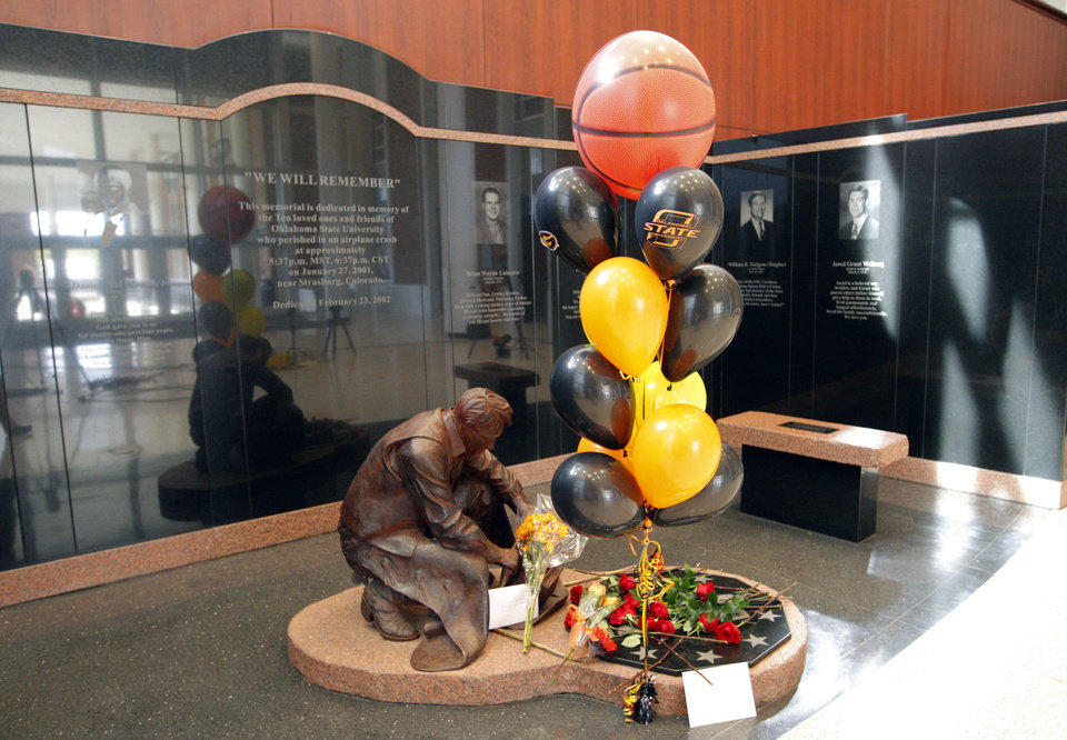 Flowers for OSU womens' head coach Kurt Budke and assistant coach Miranda Serna lay on the Remember the 10 statue at Gallagher-Iba Arena in Stillwater, Okla.,  Friday, Nov. 18, 2011.  Photo by Sarah Phipps, The Oklahoman