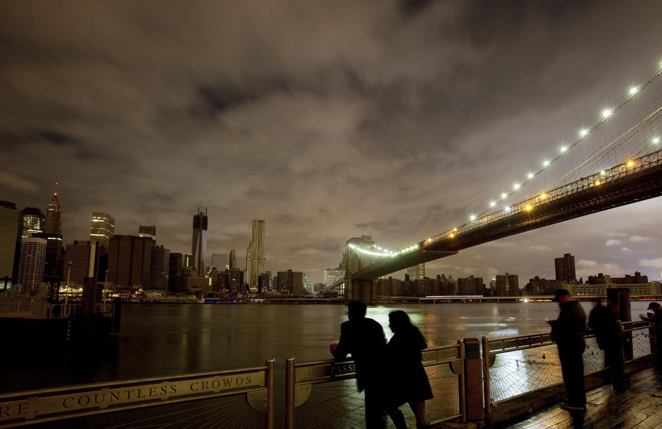 People stop along the Brooklyn waterfront to look at the Brooklyn Bridge and the Manhattan skyline, Tuesday, Oct. 30, 2012 in New York. Much of lower Manhattan is without electric power following the impact of superstorm Sandy. (AP Photo/Mark Lennihan) ORG XMIT: NYML122