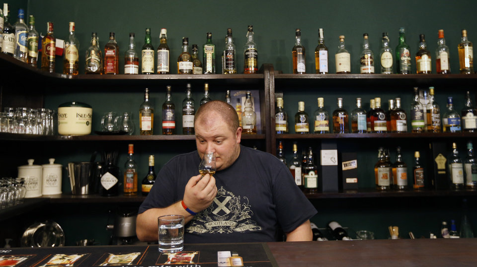 In this Thursday, April 25, 2013 photo Petr Nemy, an whisky expert, tastes the single malt