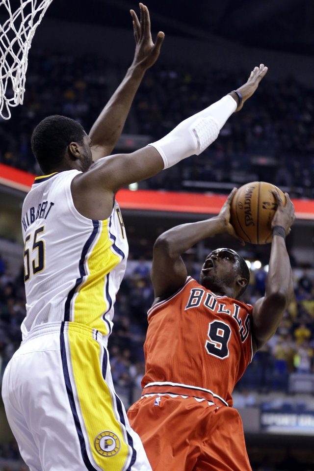 Photo - Chicago Bulls forward Luol Deng, right, attempts to shoot over Indiana Pacers center Roy Hibbert during the first half of an NBA basketball game in Indianapolis, Monday, Feb. 4, 2013. (AP Photo/Michael Conroy)
