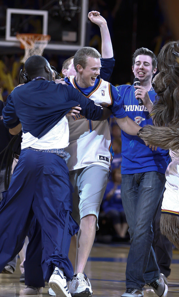 Roman Owens, center, celebrates with Rumble The Bison, right, and Oklahoma City Thunder Storm Chasers after shooting a half court shot to win $20,000 during at timeout in Game 2 of a second-round NBA basketball playoff series in Oklahoma City, Tuesday, May 3, 2011. (AP Photo/Alonzo Adams)